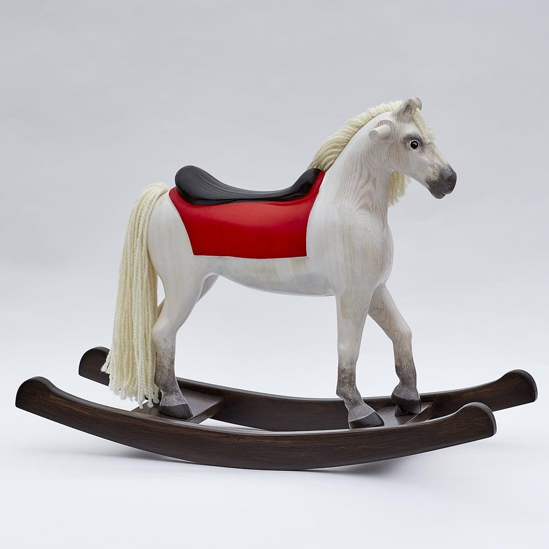 Středně velký tvarovaný houpací kůň s dřevěným sedlem bělouš