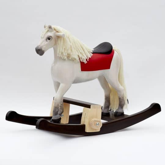 Houpací kůň vyrobený z borového dřeva nabarvený jako bělouš s podstavcem pod nohy dítěte