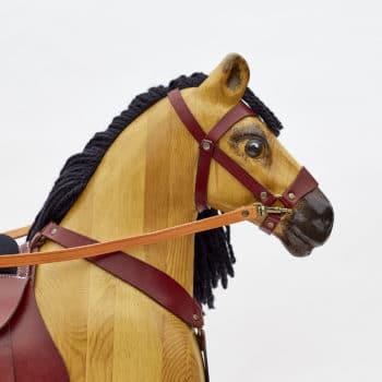 Hlava houpacího koně s koženým postrojem a vlněnou hřívou