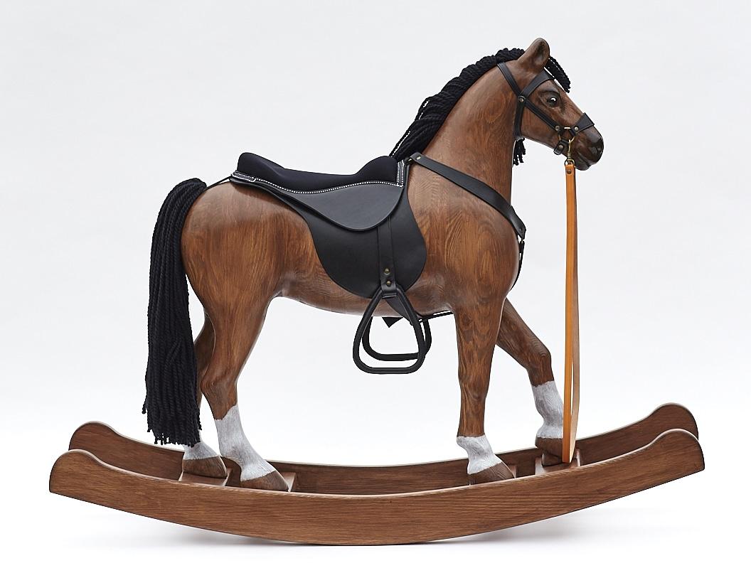 Velký dřevěný houpací kůň vyrobený z borového dřeva, věrně tvarovaný, s koženým postrojem a sedlem od sedláře.