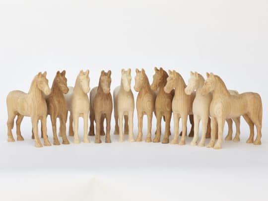 Série unikátních dřevěných koníků vyrobených z různých listnatých dřev