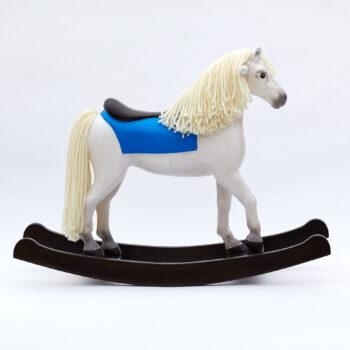 Dřevěný houpací kůň střední velikosti s dřevěným sedlem bělouš s modrým přehozem