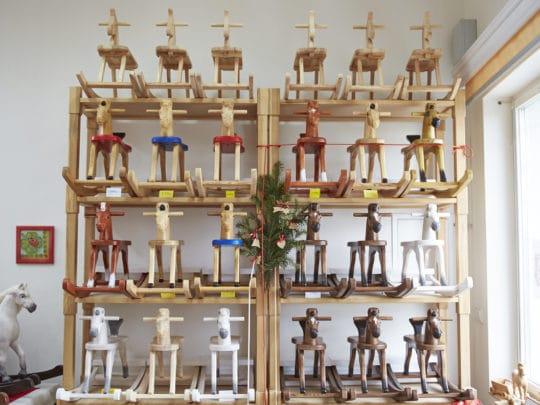 Naše kamenná prodejna s vystavenými dřevěnými houpacími koníky